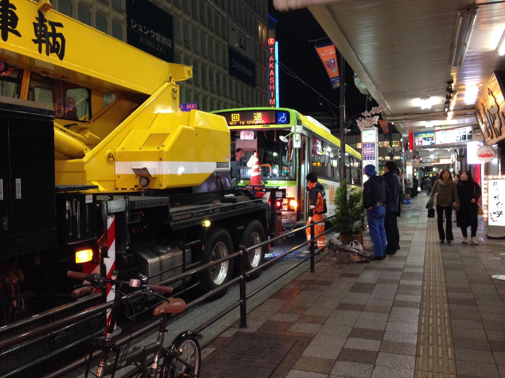 レッカー移動する国際興業バス